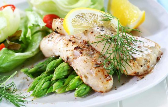 Fried fish on green asparagus